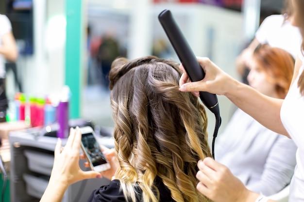 Close-up stylist maakt een meisje klant styling haar zwaaien met krultangen in een kapper