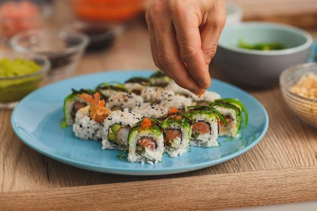 Close-up sushi-chef die rode kaviaar over rijst verspreidt terwijl hij sushi rolt, sushi-processet maakt