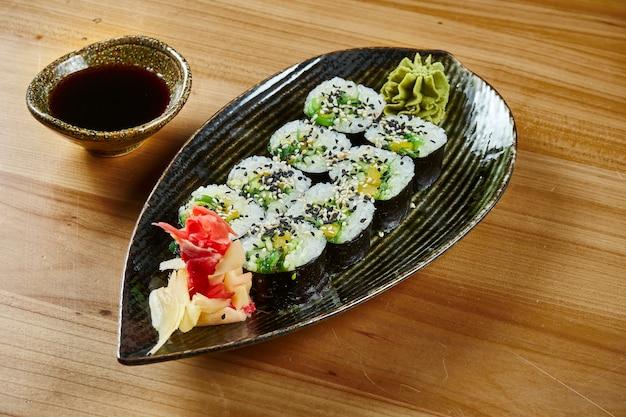 Close-up sushi roll met maki met rijst en komkommer, roomkaas op een zwarte plaat met sojasaus