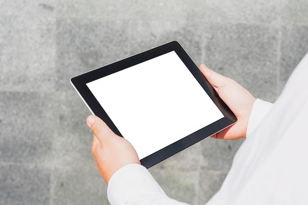 Close-up tabletmodel met een wit scherm in de handen van een zakenman tegen de achtergrond van een betonnen muur.