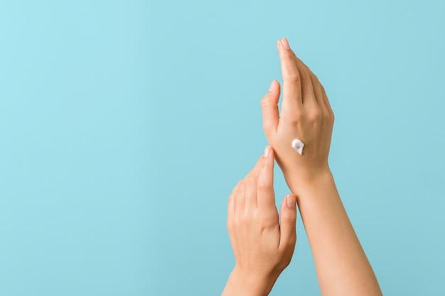 Close-up tedere hand van een jonge vrouw die bevochtigende room toepast die tegen aquablauw wordt geïsoleerd