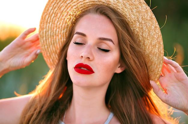 Close-up tedere portret van schoonheid sensuele vrouw poseren op veld, vintage stijl, dragen trendy strohoed, natuur schoonheid make-up, sproeten gezicht en rode volle lippen.