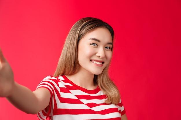Close-up tedere vrouwelijke dwaze vrouwelijke student meisje dat foto's maakt sociale media strek arm uit houden smartph...
