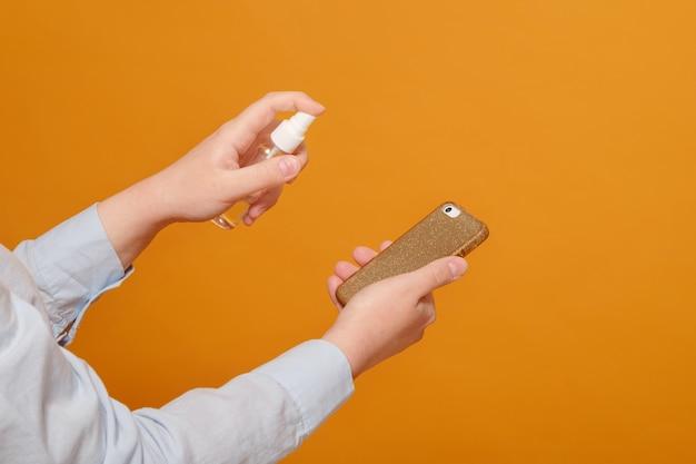 Close-up telefoon desinfectie op gele, antiseptische spray