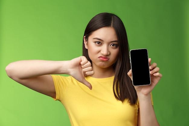 Close-up teleurgesteld overstuur aziatisch meisje beoordeelt slechte vreselijke app, toont smartphonescherm, duim omlaag grimassend ontevreden, geeft negatieve feedback, kan ex-vriendje nieuwe vriendin niet uitstaan