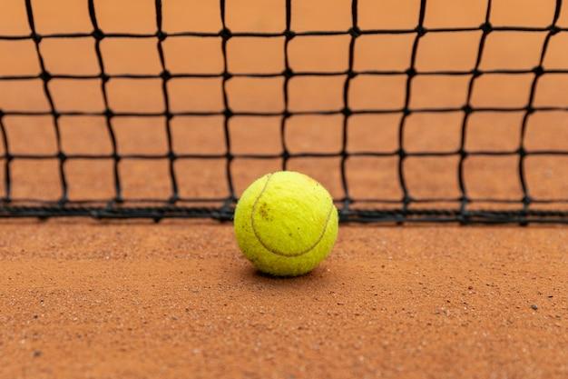 Close-up tennisbal naast net