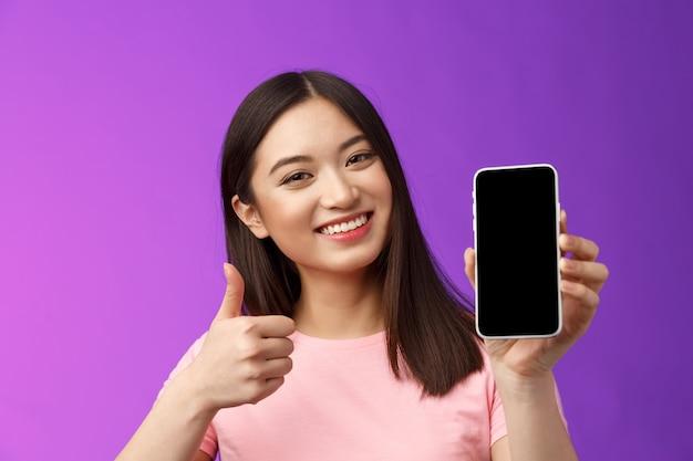 Close-up tevreden gelukkige aantrekkelijke moderne aziatische vrouw geeft positieve feedback, toont smartphone-display, introduceert goede app, steekt duim omhoog als applicatie, staat verrukt op paarse achtergrond.
