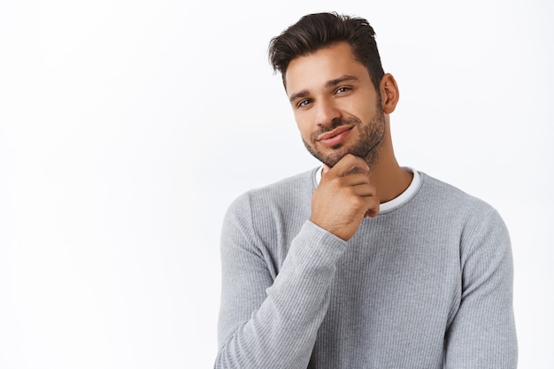 Close-up tevreden knappe bebaarde man maakte zijn keuze, trots of tevreden met een goede beslissing, wrijvende kin glimlachend in goedkeuring, overeenkomst expressie, zoals idee wat vriendin kopen voor b-day cadeau