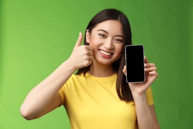 Close-up tevreden schattig aziatisch meisje geeft positieve feedback, duim omhoog met smartphonescherm, introduceert geweldige nieuwe app, raad een goede applicatie aan, opscheppende beatscore in het spel.
