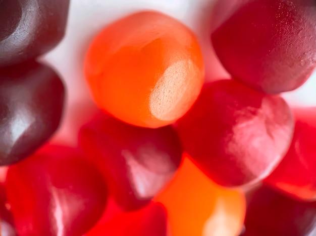 Close-up textuur van rode, oranje en paarse multivitamine gummies. gezond levensstijlconcept.