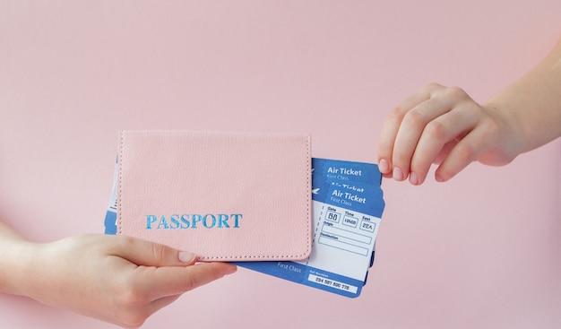 Close-up toeristische vrouwelijke horizontale in de hand houden kaartjes voor vliegtuig met oranje paspoort, instapkaart, geïsoleerd op geel