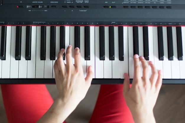 Close-up top shot van een klassieke muziek vrouwelijke hand piano of elektronische synthesizer spelen (piano keyboard)
