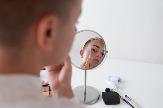 Close-up transgender in de spiegel kijken
