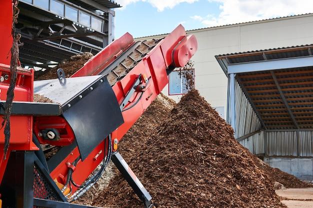 Close-up transportband van een industriële houtversnipperaar die houtsnippers produceert uit schors