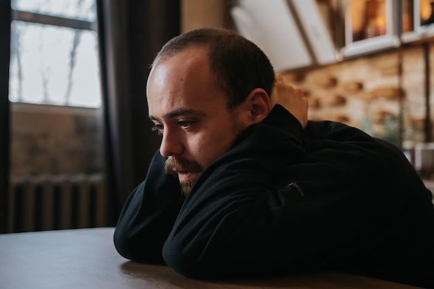 Close-up trieste en depressieve bebaarde man in het donker, wanhopige man alleen, op de tafel in de keuken, in het huis, binnenshuis