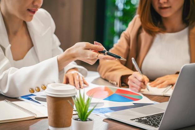 Close-up twee aziatische zakenvrouwen werken met de partner business per punt vinger naar de technologie laptop in moderne vergaderruimte, kantoor of werkruimte, koffiepauze, partner en collega concept