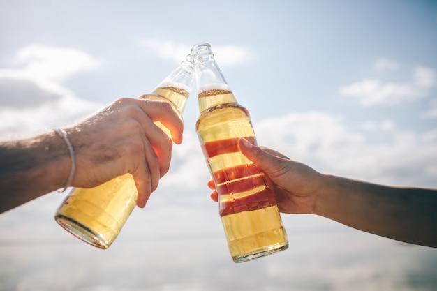 Close-up twee flessen met bier in handen in de zon tegen de hemel.