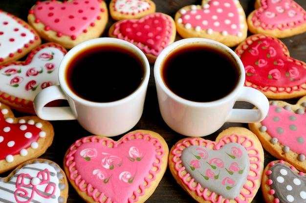 Close-up twee kopjes hete koffie onder hoop zelfgemaakte hartvormige koninklijke suikerglazuur schattig patroon koekjes