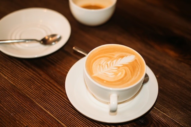 Close-up twee kopjes koffie, plaat en lepel op houten tafel.