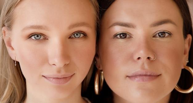 Close-up twee portretgezichten van gemengde raced vrouwen kijken van dichtbij. jonge blonde en brunette.