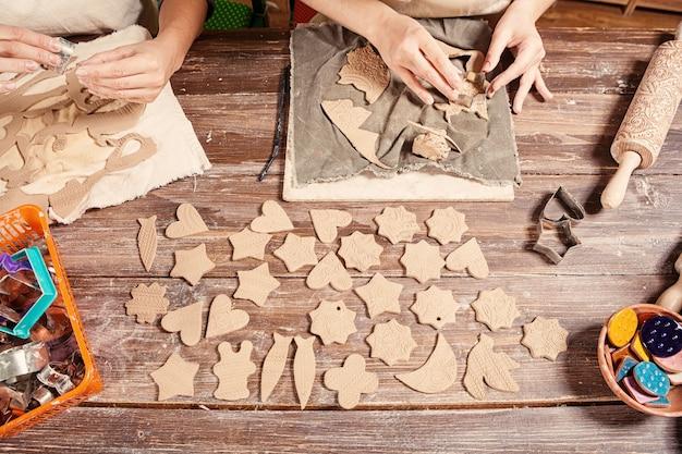 Close-up twee vrouwelijke pottenbakkers maken veel kerstspeelgoed met behulp van formulieren
