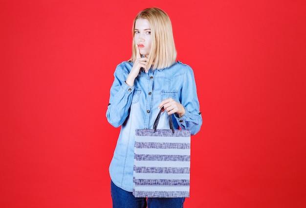 Close-up twijfelachtige jonge vrouw met boodschappentas en staande op rode muur