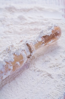 Close-up uitzicht op houten deegroller op wit natuurlijk meel eten en drinken concept
