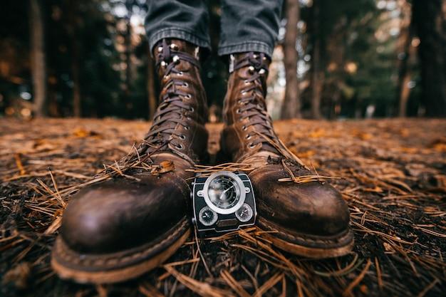 Close-up uitzicht op mannelijke benen in vintage lederen laarzen en horloges in herfst park
