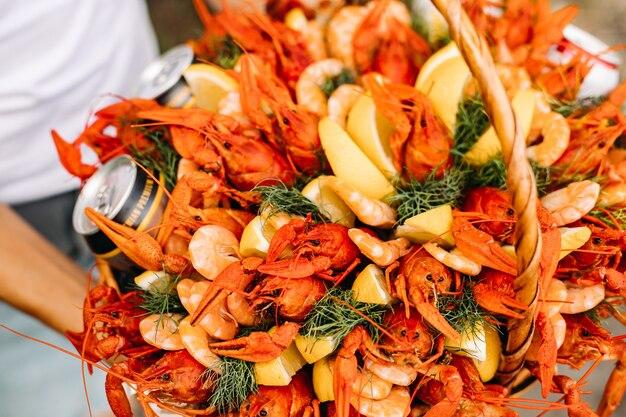 Close-up uitzicht over een feestelijke mand vol verse en smakelijke rivierkreeftjes, garnalen en bierblikjes versierd met schijfjes citroen en trossen dille.