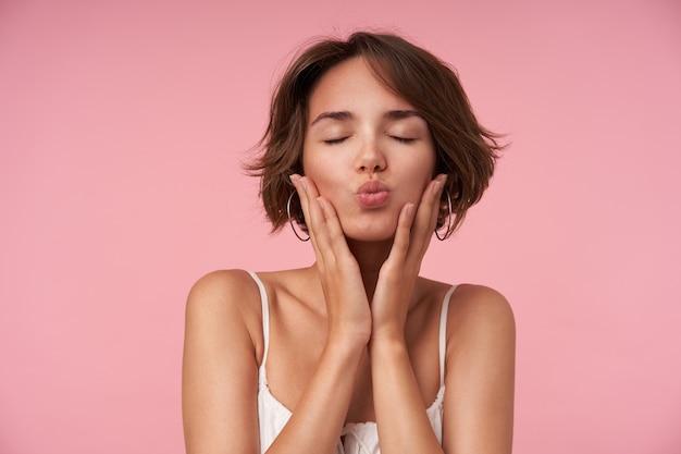 Close-up van aangenaam uitziende brunette vrouw met kort kapsel poseren met gesloten ogen, haar gezicht met opgeheven handen vasthouden en lippen vouwen in kus