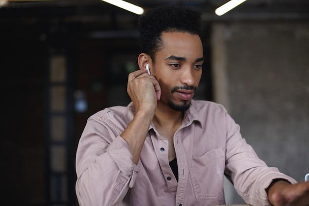 Close-up van aantrekkelijke donkere man met baard en kort kapsel oortje invoegen in zijn oor en vooruitkijken met kalm gezicht, casual kleding dragen terwijl poseren boven stadscafé