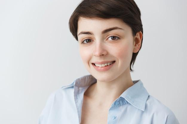 Close-up van aantrekkelijke dromerige vrouw die met hoopvolle glimlach kijkt