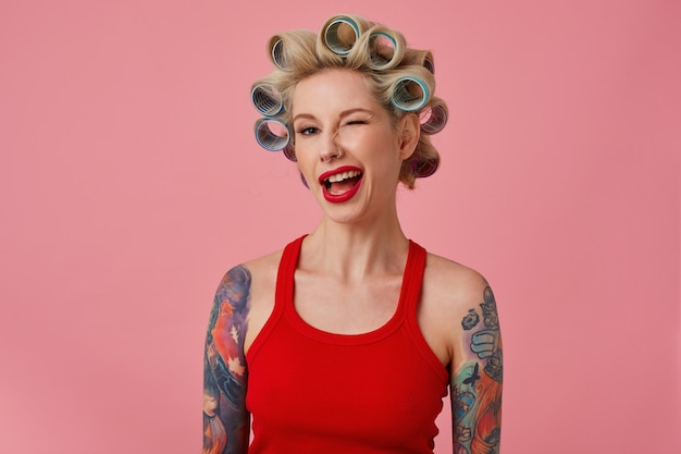 Close-up van aantrekkelijke jonge blonde getatoeëerde vrouw die kapsel maakt tijdens de voorbereiding voor vakantieviering, positief knipogend naar de camera terwijl staande op roze achtergrond met krulspelden op haar haar