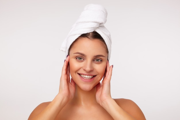 Close-up van aantrekkelijke jonge dame met donker haar gewikkeld in een badhanddoek die haar gezicht aanraakt met opgeheven handen en vrolijk kijkt met een brede glimlach, staande tegen een witte achtergrond