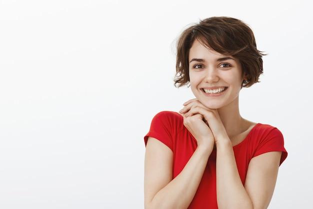 Close-up van aantrekkelijke jonge vrouw die dankbaar en opgetogen kijkt, tevreden glimlacht
