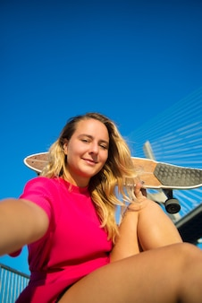 Close-up van aantrekkelijke jonge vrouw die selfie neemt. mooi lachend meisje in karmozijnrode jurk met skateboard zitten in de buurt van de brug, het nemen van foto's van zichzelf.
