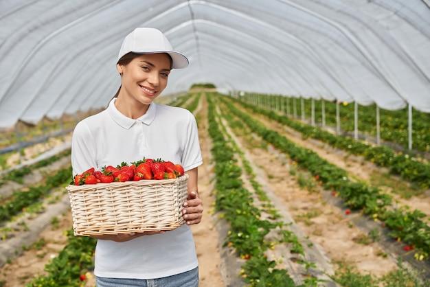 Close up van aantrekkelijke jonge vrouw in witte dop met grote witte rieten mand met rijpe smakelijke aardbeien in kas. concept van het bewonderen van een goede oogst.