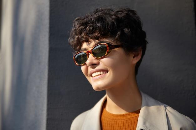 Close-up van aantrekkelijke krullende donkerharige vrouw met casual kapsel poseren over de betonnen muur van de stad in vintage zonnebril, vrolijk opzij kijken met charmante glimlach