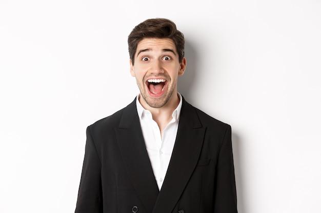 Close-up van aantrekkelijke man in zwart pak, verbaasd glimlachend en kijkend naar advertentie, staande op een witte achtergrond