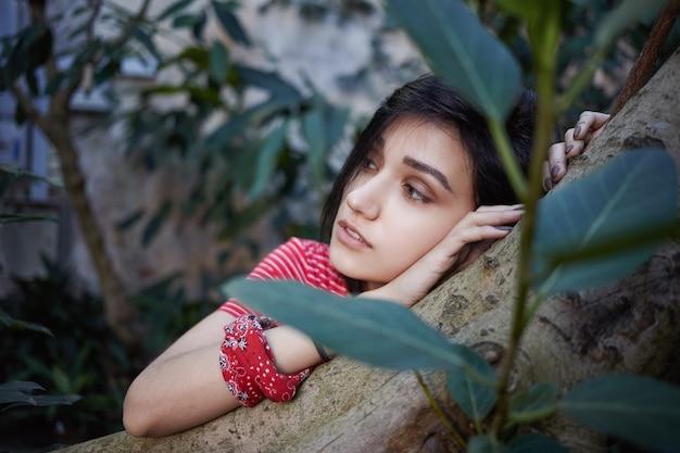 Close-up van aantrekkelijke romantische jonge dame met bob kapsel haar hoofd rustend op boomstam en zijwaarts kijken met dromerige doordachte gezichtsuitdrukking. selectieve aandacht voor het gezicht van het meisje