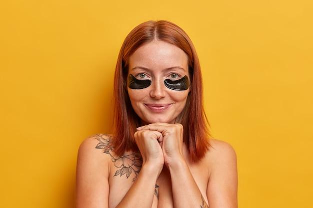 Close-up van aantrekkelijke vrouw met rood haar, houdt de handen onder de kin, heeft dagelijkse verwenningsroutine, past vochtinbrengende ooglapjes toe, verzorgt de huid, staat shirtless poses tegen gele muur