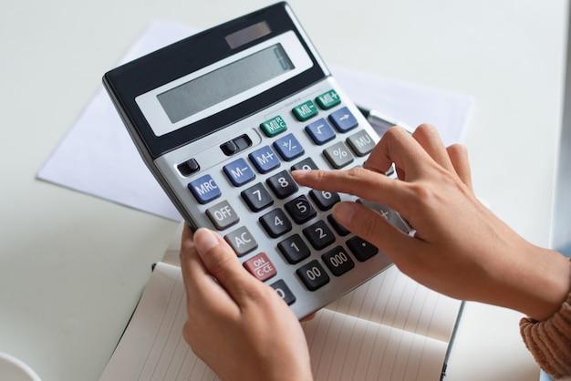 Close-up van accountant die calculator gebruikt terwijl het onderzoeken van rapport