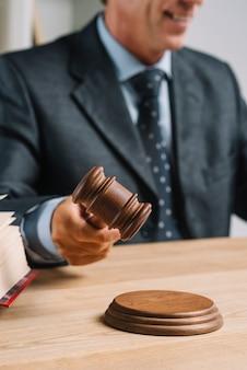 Close-up van advocaat die de houten hamer op klinkend blok slaan bij houten bureau