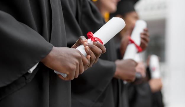 Close-up van afgestudeerden met diploma's