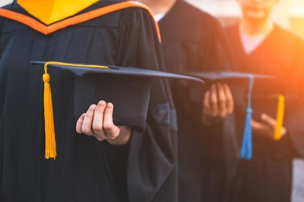 Close up van afgestudeerden met hoeden in de hand