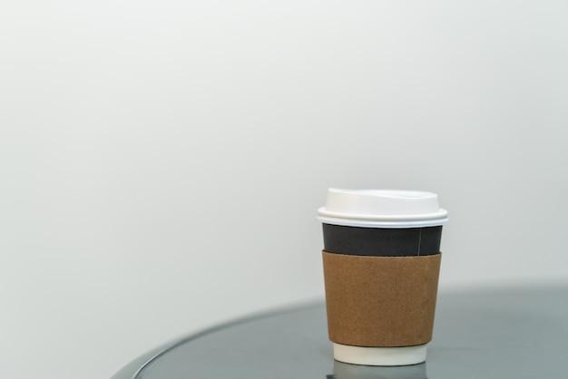 Close-up van afhaalmaaltijden papieren beker met mouw warme koffie op ronde tafel met kopie ruimte.