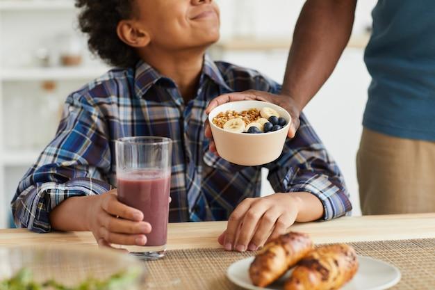 Close-up van afrikaanse jongen granen eten en drinken van vers sap voor ontbijt bereid door zijn vader