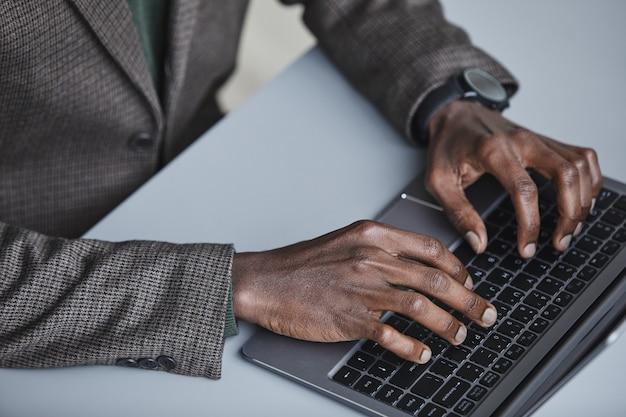 Close-up van afrikaanse kantoormedewerker typen op toetsenbord van laptopcomputer aan de tafel