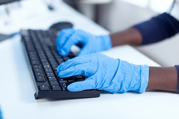Close up van afrikaanse onderzoeker hand in hand op het toetsenbord van de computer zwarte gezondheidszorg wetenschapper in biochemie laboratorium steriele apparatuur dragen.