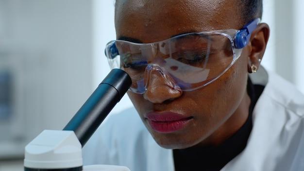 Close up van afrikaanse vrouw arts die virus analyseert met behulp van de microscoop. multi-etnisch team dat de evolutie van vaccins onderzoekt met behulp van hightech voor wetenschappelijk onderzoek naar de ontwikkeling van behandelingen tegen covid19